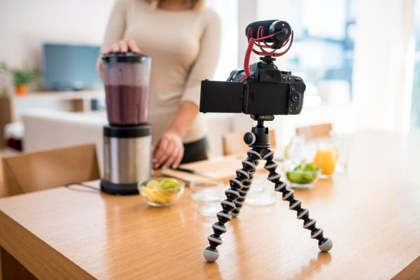 A close up of a young woman vlogging herself whilst preparing a smoothie